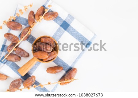 Dates fruit in wooden ladle on white background,Dried date palm fruits top view #1038027673