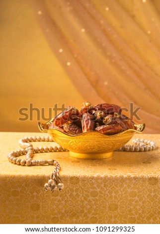 Dates in a decorative golden bowl with Islamic rosary. Beautiful Ramadhan greetings background. #1091299325