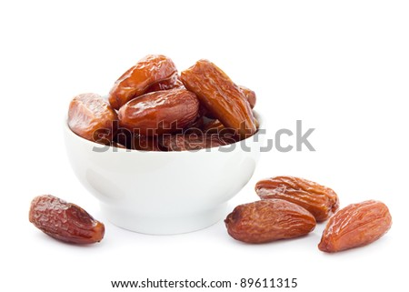 Dates in a white bowl on a white background.