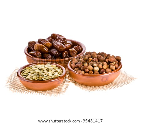 Dates, pumpkin seeds and hazelnuts in ceramic dishes isolated on white background