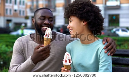 Dating couple eating ice-cream, sitting on city bench, having fun together, love