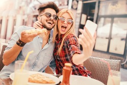Dating in pizzeria. Handsome smiling couple enjoying in pizza, having fun together. Consumerism, food, lifestyle concept