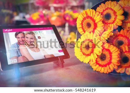 Dating website against digital tablet with yellow flowers