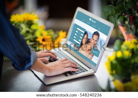 Dating website against female florist using laptop in flower shop