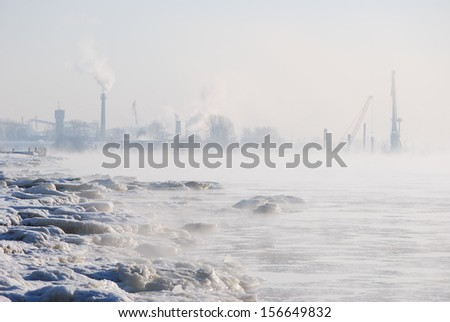 Daugava river in a cold winter day. Hoar frost and mist