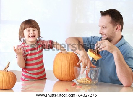 Daughter and father carving pumpkin for Halloween