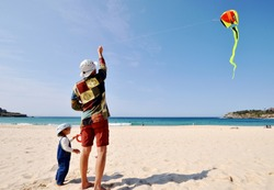 Daughter and father riding a kite on Bondi beach in Sydney, Australia