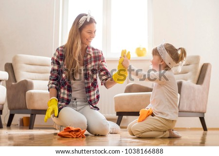 Daughter and mother cleaning home together and having fun.