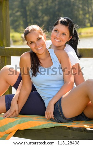 Daughter and mother sitting on pier relaxing smiling teen comfortable