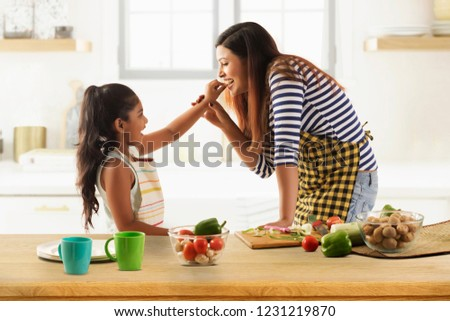 Daughter feeding cucumber to her mother in kitchen