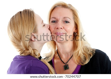 Daughter gives mother a kiss on the cheek over white background