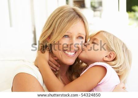 Daughter Giving Mother Kiss Relaxing On Sofa
