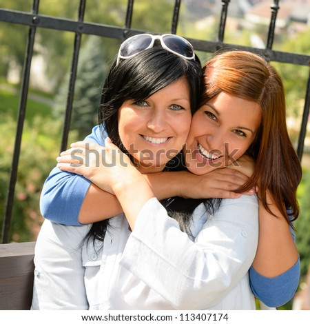 Daughter hugging her mother outdoors happy loving teen bonding affectionate