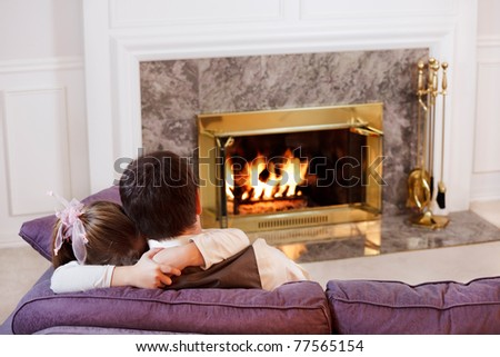Daughter hugs her Dad by the light of a warm fire