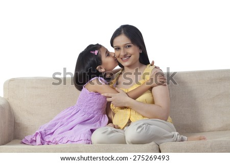 Daughter kissing pregnant mother