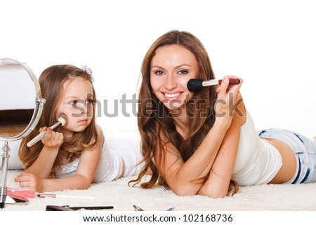 Daughter looks at mother applying makeup