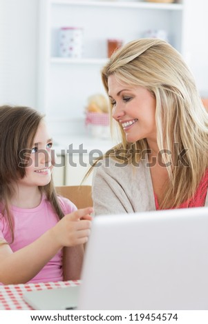 Daughter pointing at laptop with her mother in kitchen