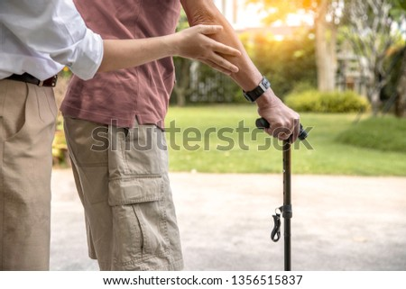 Daughter's hand holding father's hand  walking  with walking stick. ,Love and family concept. - Image #1356515837