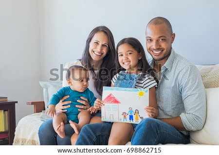 Daughter showing drawing of a happy family in new house. Cute infant looking at colorful drawing of his sister. Happy proud multiethnic parents sitting with children on sofa  and looking at camera.