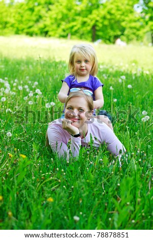 Daughter sits on mother on a grass outdoors smiling