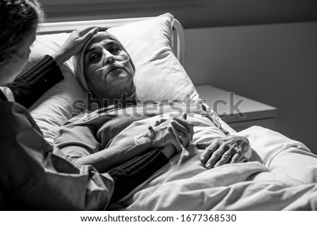 Daughter supporting sad, dying woman with tumor in a hospital, black and white photo Stock foto ©
