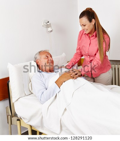 Daughter vising her old father at sickbed in hospital