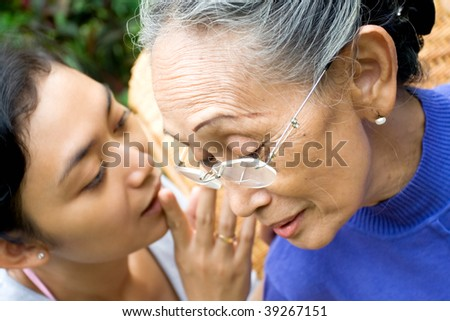 daughter whispering some serious issue to her old mother