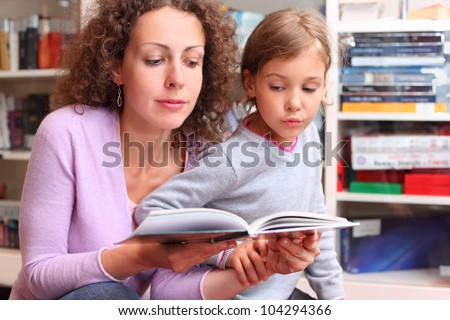 Daughter with her mother read book in room with bookshelves; focus on woman