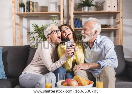 Daughter with her older parents singing a favorite song on a karaoke microphone