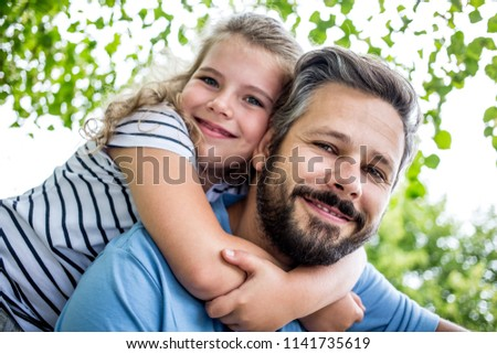 Daugther embrace father in piggyback ride at the park