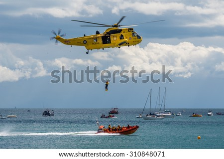DAWLISH, UNITED KINGDOM - AUGUST 23, 2014: Royal Navy Sea King Search and Rescue Helicopter Flying at the Dawlish Airshow Demonstrating Winch Rescue with an Inshore Lifeboat