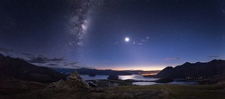 Dawn at Lake Wanaka in New Zealand under the milky way in a stary sky with a rising full moon.