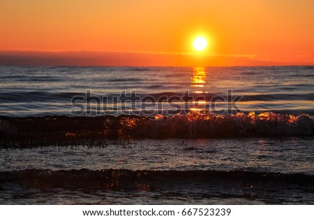 Dawn at the Ladoga. The sun rising above the lake reflecting in the waves.