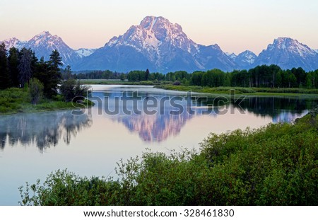 Dawn colors on snow capped mountains in the Grand Tetons. #328461830