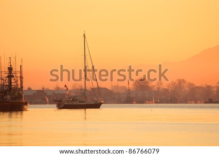 Dawn in Steveston, British Columbia, Canada where a sailboat casts off for a day of sailing. Located at the mouth of the Fraser River near Vancouver