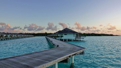 Dawn in the Maldives. A wooden walkway runs over the aquamarine ocean, next to the water villas. In the distance, the shore of the island, palm trees. There are pink clouds in the gentle blue sky.