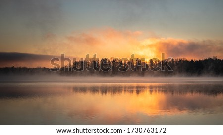 Dawn landscape at Lake Ontelaunee over a forested shore with fog at the water's surface Stock photo ©