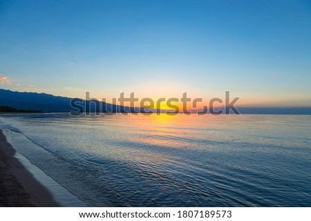 Dawn of the sun at sea. The rising sun behind the mountains. Photo stock ©
