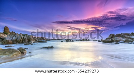 Dawn on the beach with brightly colored clouds, beneath a rock with beautiful shapes create beautiful scenery welcome bright day fresh #554239273