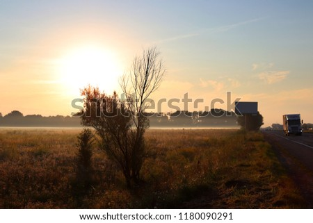 Dawn outside the city. Autumn begins. A huge sun rises over the yellowed grass. Morning fog. On the road there are cars and trucks #1180090291