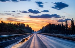 Dawn over the forest highway. Highway road at dawn. Sunrise over highway road. Road at dawn