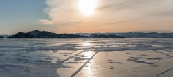 Dawn over the winter island of ice-covered Lake Baikal in Russia with car traces on ice