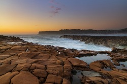 Dawn seascape from tessellated rock platform at North Avoca Beach on the Central Coast, NSW, Australia.