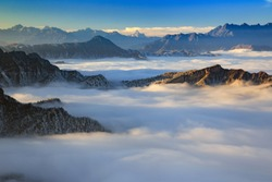 Dawn, Sunrise above the clouds - Niubeishan Landscape, Cattle Back Mountain, Sichuan Province China. Snow mountains, Ice Frost and Rime. Frozen Winter Landscape, Frigid Cold Atmosphere. Sea of Clouds