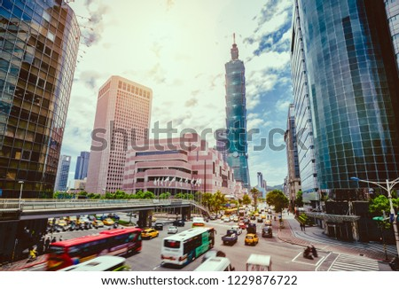 Dawn view of a pedestrian footbridge over a busy street corner in Taipei City with Taipei 101 Tower and World Trade Center in Xinyi District ~ Beautiful scenery of Taipei Downtown at rush hour