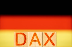 dax index concept. wooden blocks with the word dax on the background of the national flag of germany