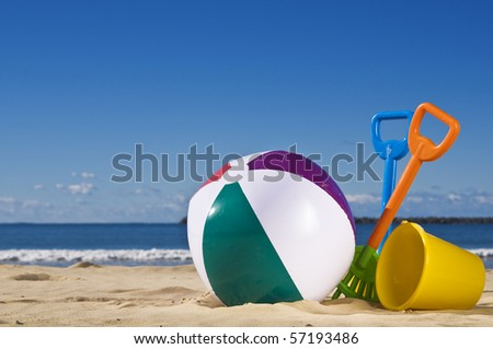 Day at the beach with a beach ball, spade and bucket in the foreground. - stock photo