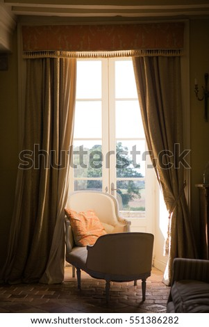 day bed by window in parlor in central France chateau  #551386282