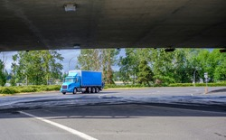 Day cab professional big rig blue semi truck with spoiler on the roof transporting commercial cargo in dry van box trailer running on the crossroad turning under the bridge