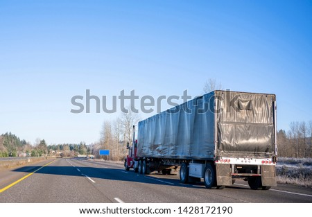 Day cab red classic popular powerful industrial grade big rig semi truck transporting commercial cargo in black covered semi trailer running on the straight wide highway in sunny day #1428172190